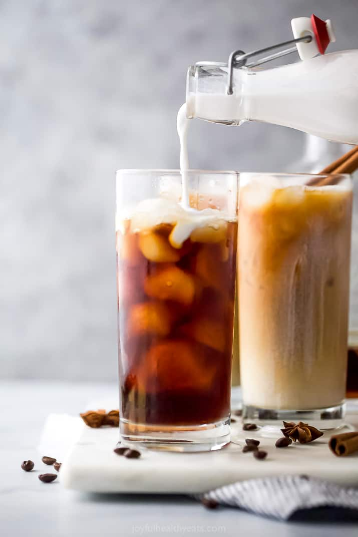pouring coconut milk into an iced chai tea latte cup
