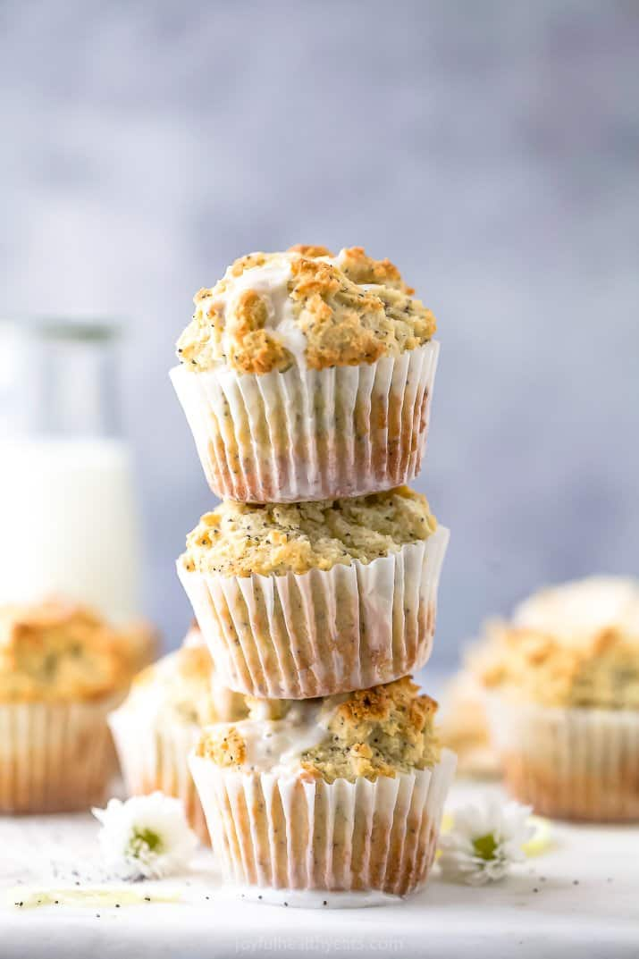 close up of moist gluten free lemon poppyseed muffins stacked on top of each other