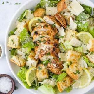 a bowl filled with easy grilled chicken caesar salad with homemade dressing
