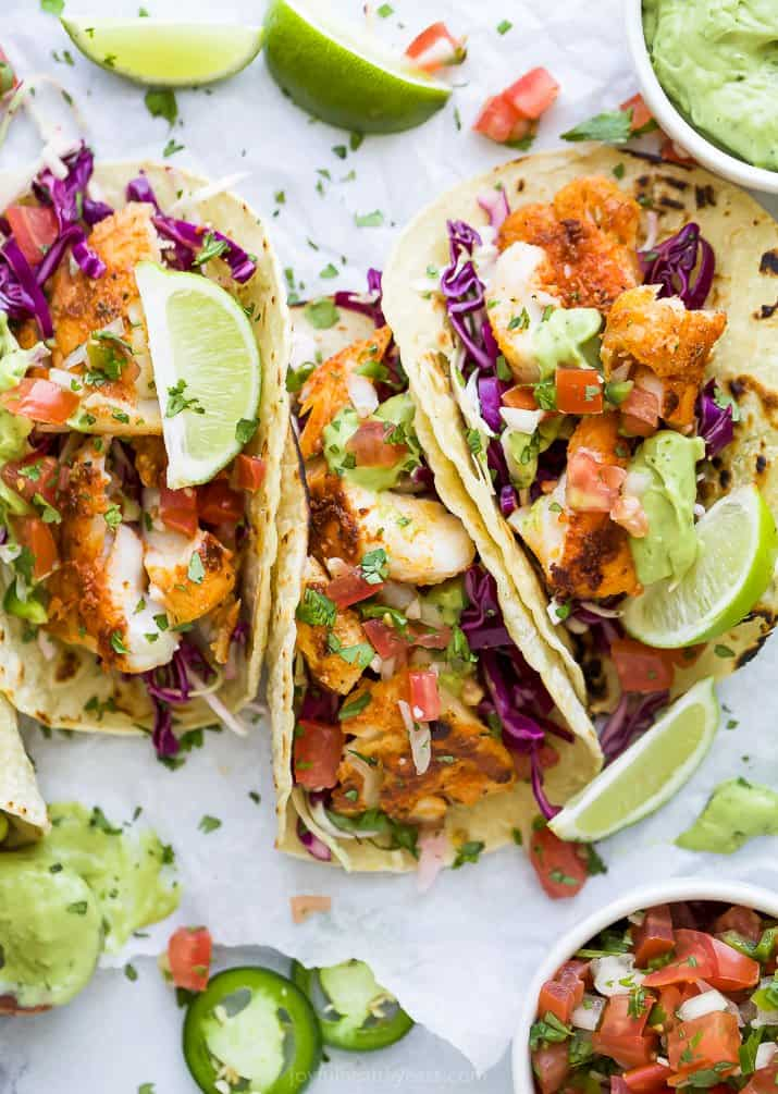 overhead photo of epic baja fish tacos with an avocado crema and lime wedges