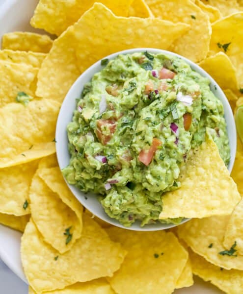 the best guacamole recipe in a bowl with tortilla chips around it