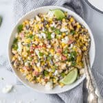 a bowl of grilled mexican street corn salad topped with fresh cilantro
