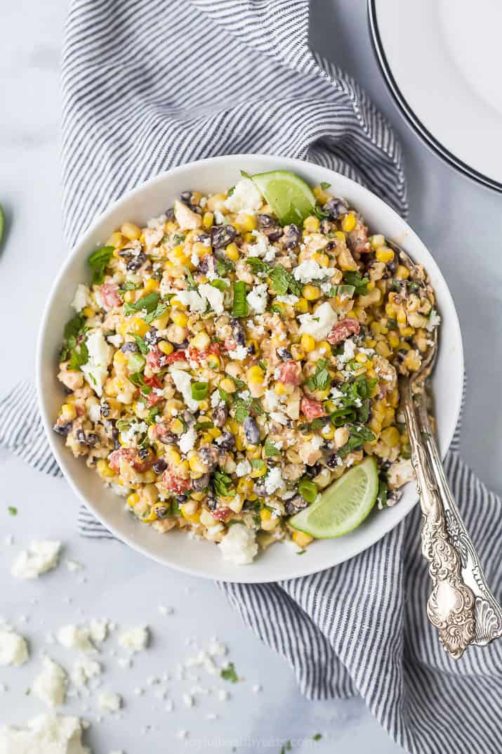 a bowl of grilled mexican street corn esquites salad topped with fresh cilantro