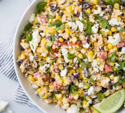 a bowl filled with grilled mexican street corn salad topped with limes