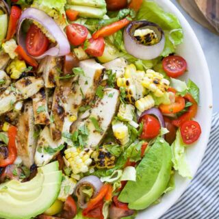 a bowl filled with a grilled honey mustard chicken salad with avocado and veggies