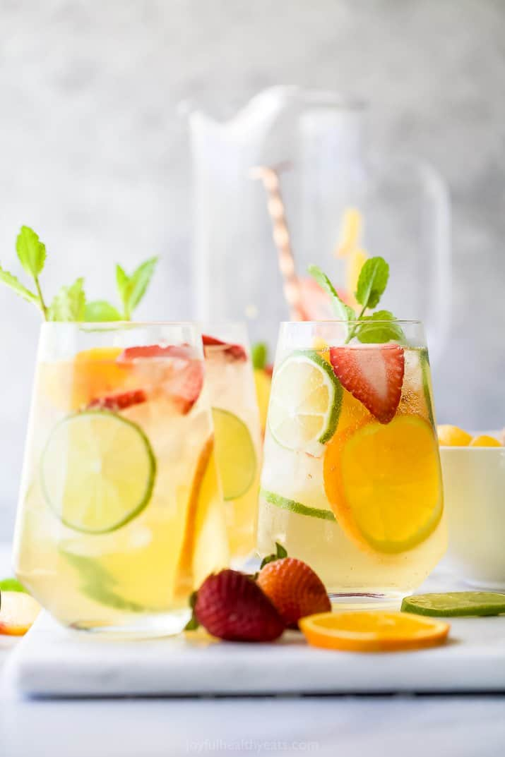 glasses filled with moscato sangria garnished with peaches and strawberries