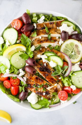 light greek salad with grilled chicken in a bowl topped with greek dressing