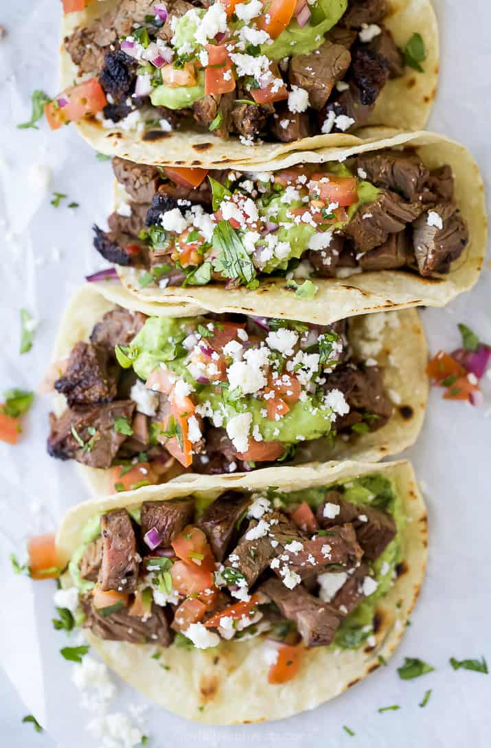 four best ever marinated carne asada tacos bunched up together and topped with pico de gallo and avocado crema