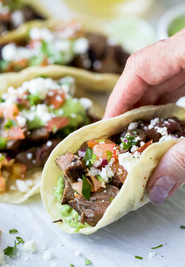 a hand holding a corn tortilla filled with carne asada taco meat and avocado crema