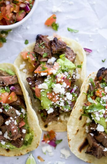 corn tortillas filled with marinated carne asada meat and avocado crema