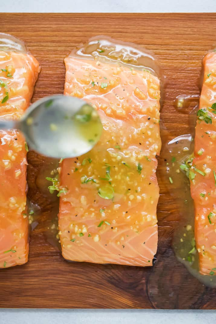 honey garlic sauce being poured on cedar plank salmon
