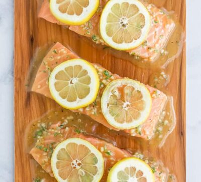 honey garlic cedar plank salmon topped with lemon slices