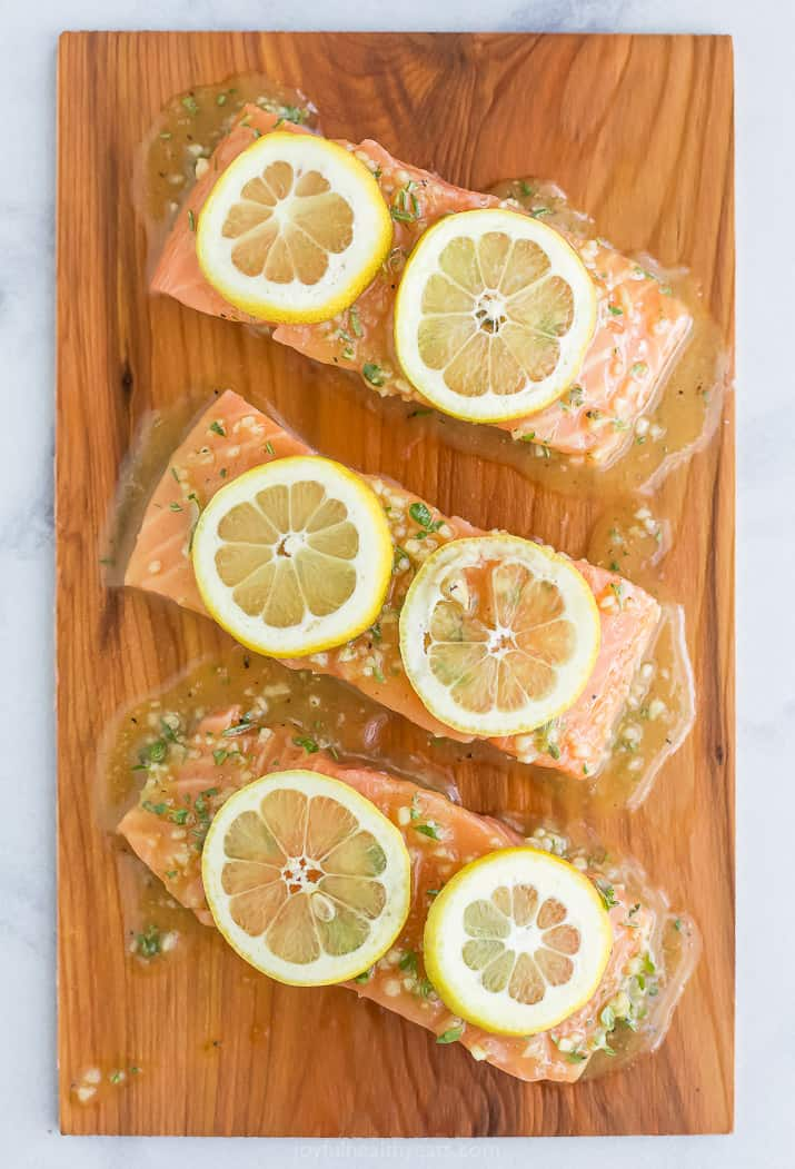 cedar plank salmon with honey garlic sauce and lemon slices on it