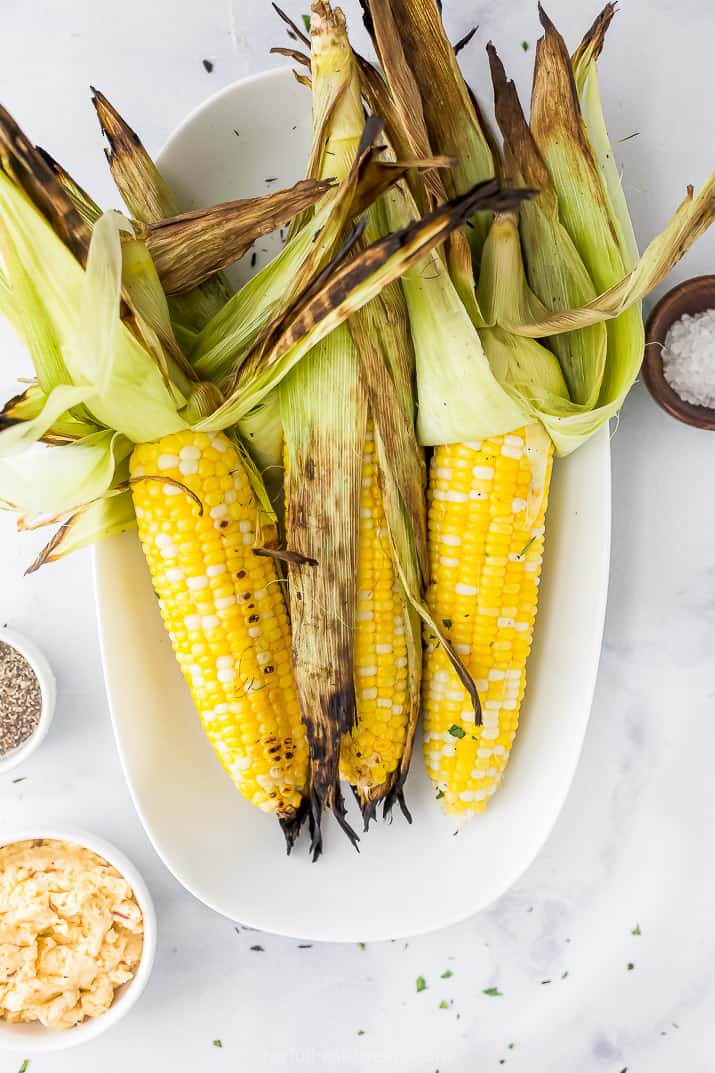 grilled corn on the cob topped with honey chipotle butter on a plate
