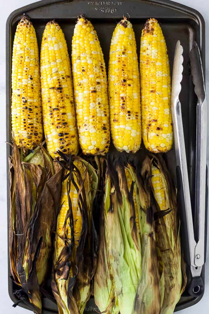a baking sheet filled with grilled corn on the cob