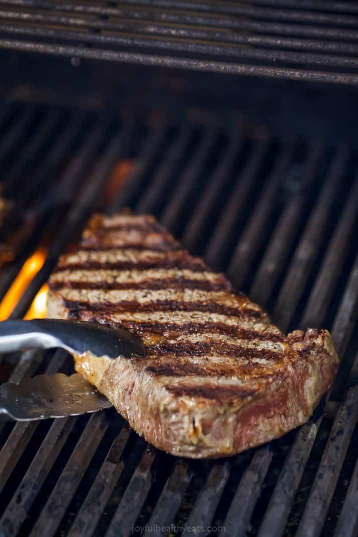 ribeye steak being grilled and held by tongs