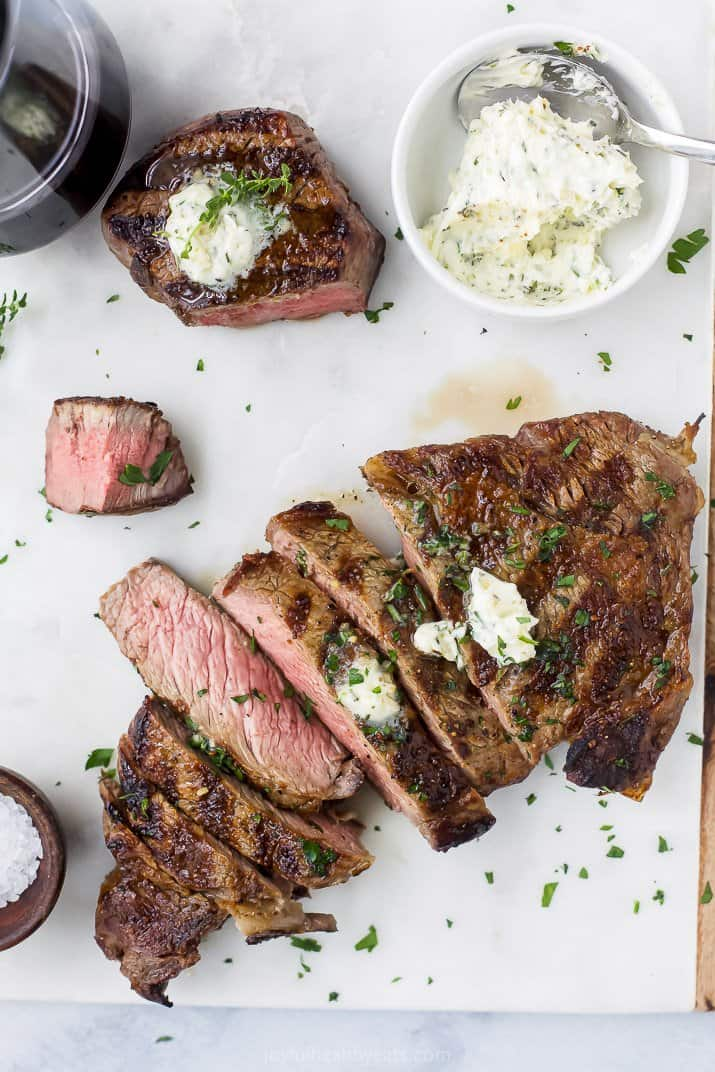overhead photo of perfectly grilled ribeye steak and filet mignon with herb butter on top