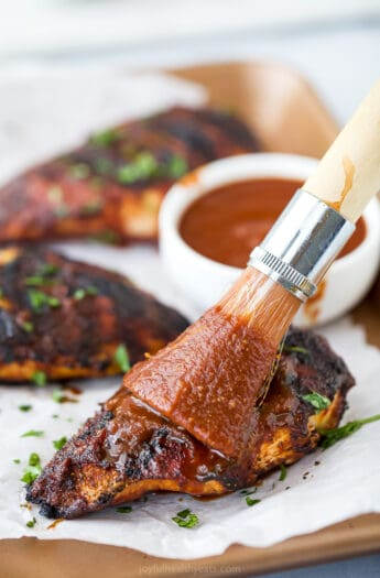 bbq sauce being brushed on bbq chicken