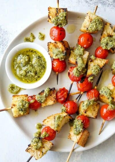grilled bruschetta skewers on a plate with ricotta pesto