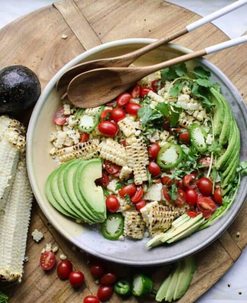 a bowl filled with grilled corn and avocado salad