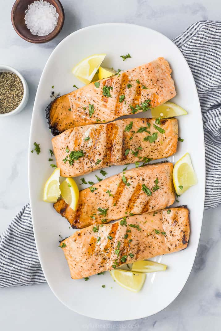 grilled salmon on a plate topped with lemon slices and fresh herbs