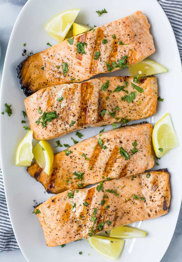 closeup photo of grilled salmon topped with lemon and fresh herbs