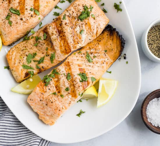 grilled salmon on a plate topped with lemon and fresh herbs