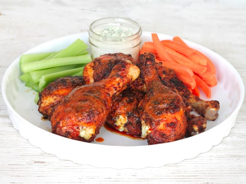 a plate filled with grilled buffalo blue cheese drumsticks