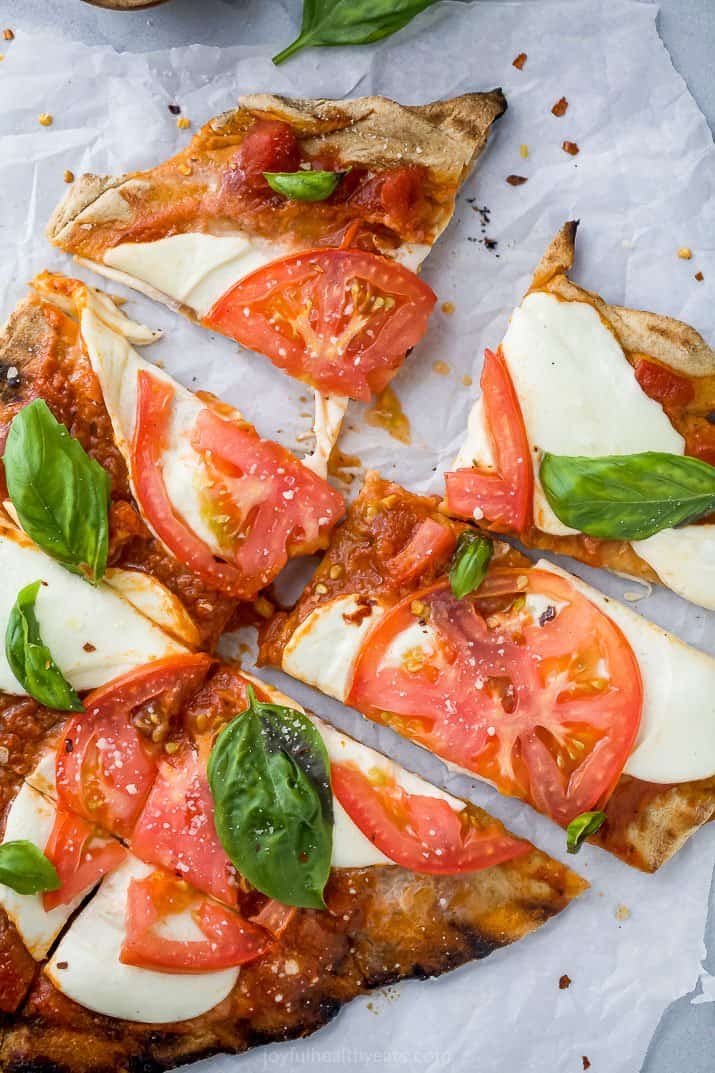 cut up pieces of the best grilled pizza recipe with margherita toppings