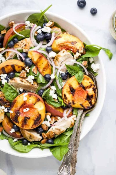 the ultimate grilled peach chicken salad in a bowl with honey mustard dressing