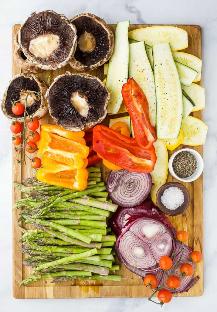raw vegetables on a cutting board ready to grill