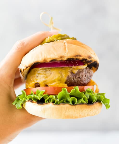 hands holding the best grilled burger topped with lettuce tomato onion and pickles