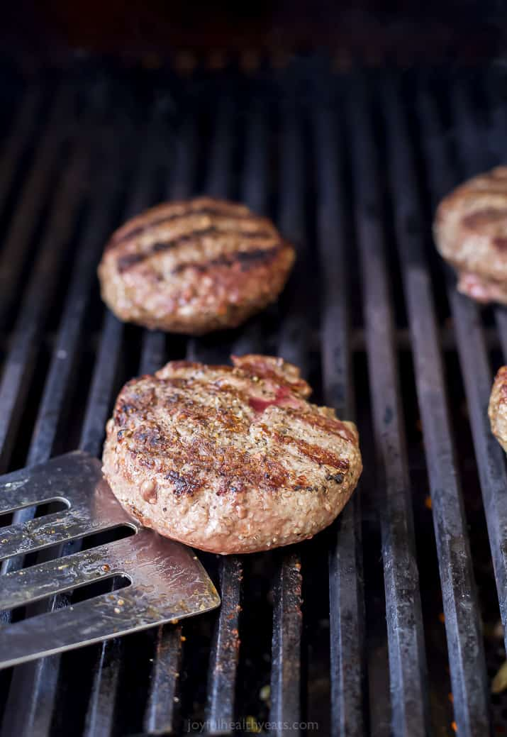 burgers being grilled on a gas grill with a spatula getting ready to flip