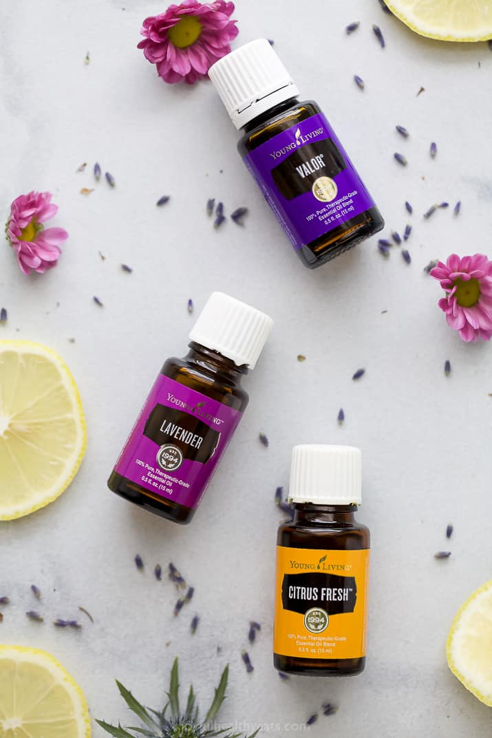 essential oils laid on a table with flowers around them