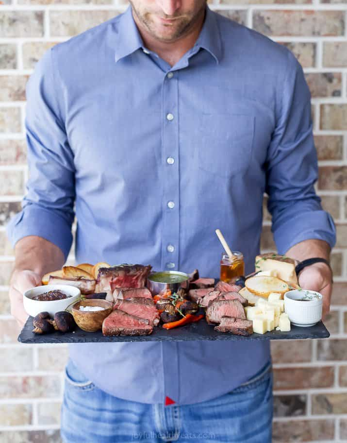 man holding a steak charcuterie board