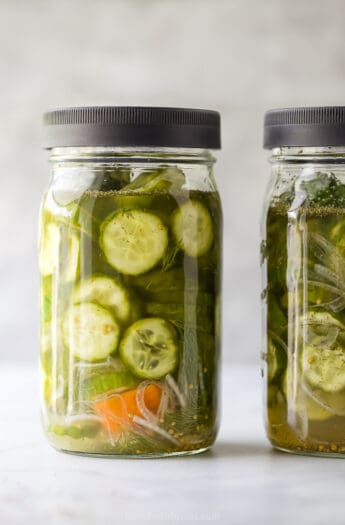 a mason jar filled with dill pickles and habanero peppers