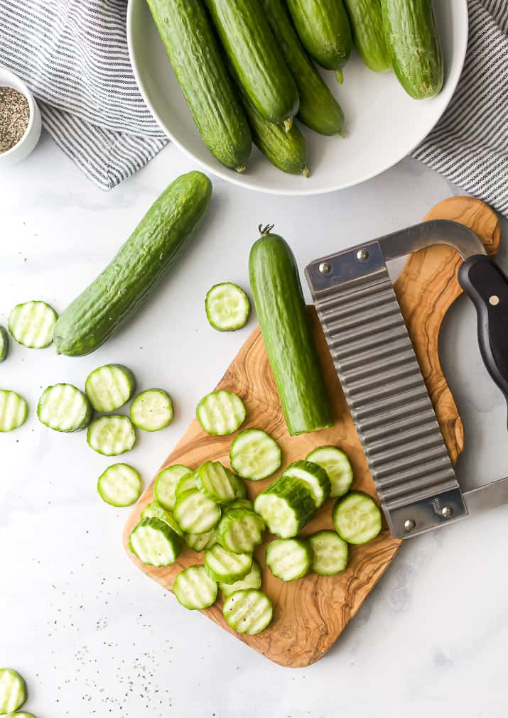 cucumbers sliced into coins on a cutting board