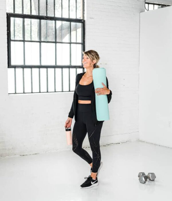 girl in workout gear holding a yoga mat