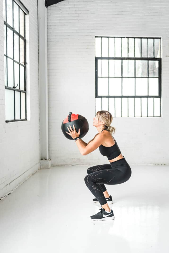 girl doing a squat with a wall ball