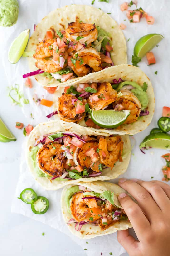 a hand grabbing a taco filled with shrimp and cabbage slaw