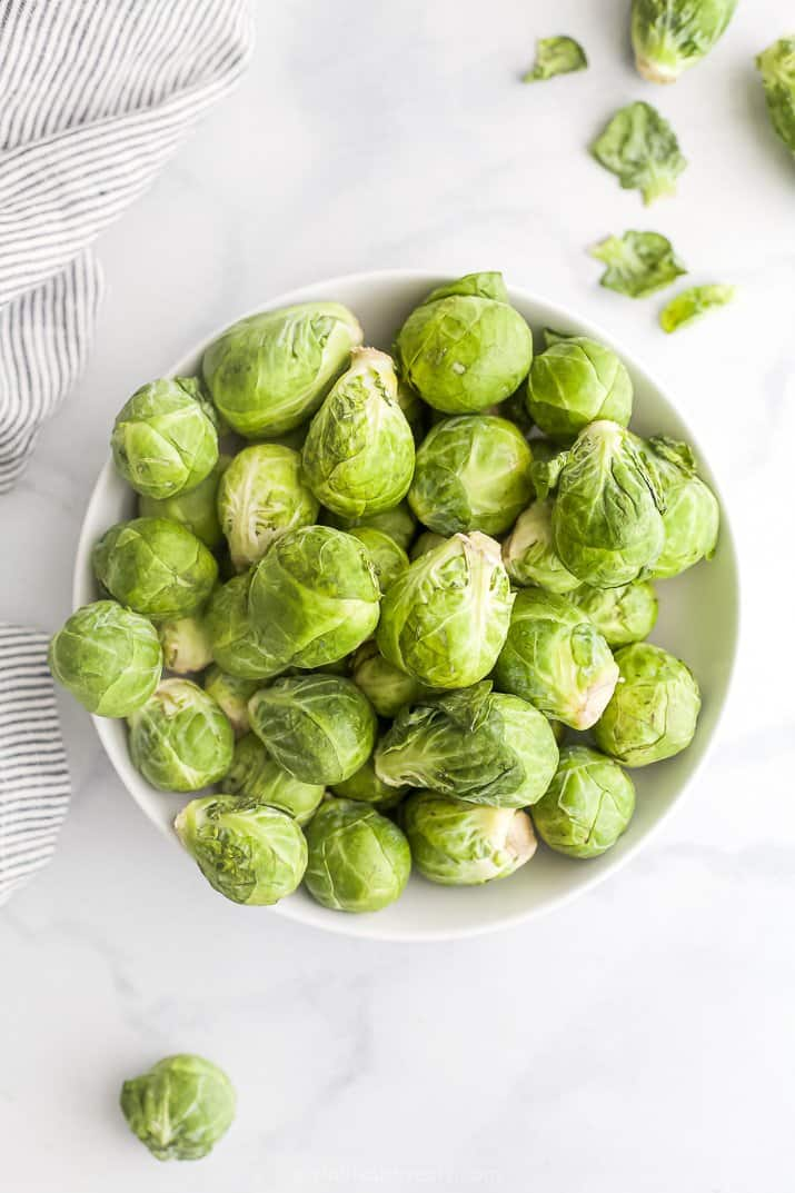 a bowl filled with raw brussel sprouts