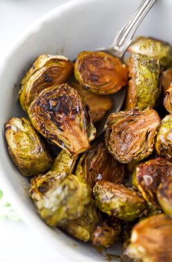 closet up of oven roasted brussel sprouts with balsamic in a bowl