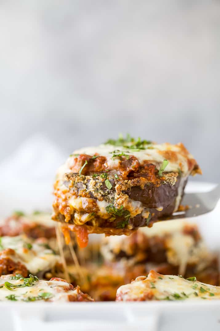 eggplant parmesan being pulled from a baking dish