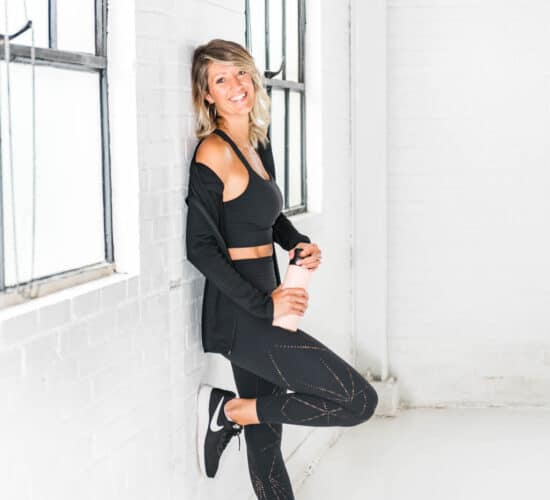 A woman in exercise clothes leaning against a gym wall