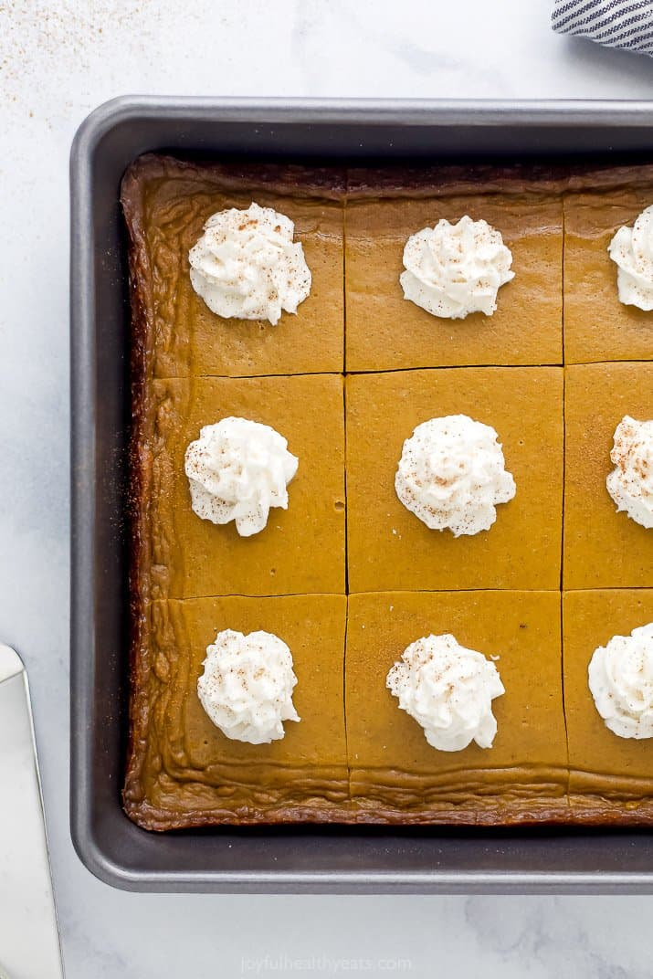 pumpkin pie bars in a baking dish topped with almond milk whipped cream