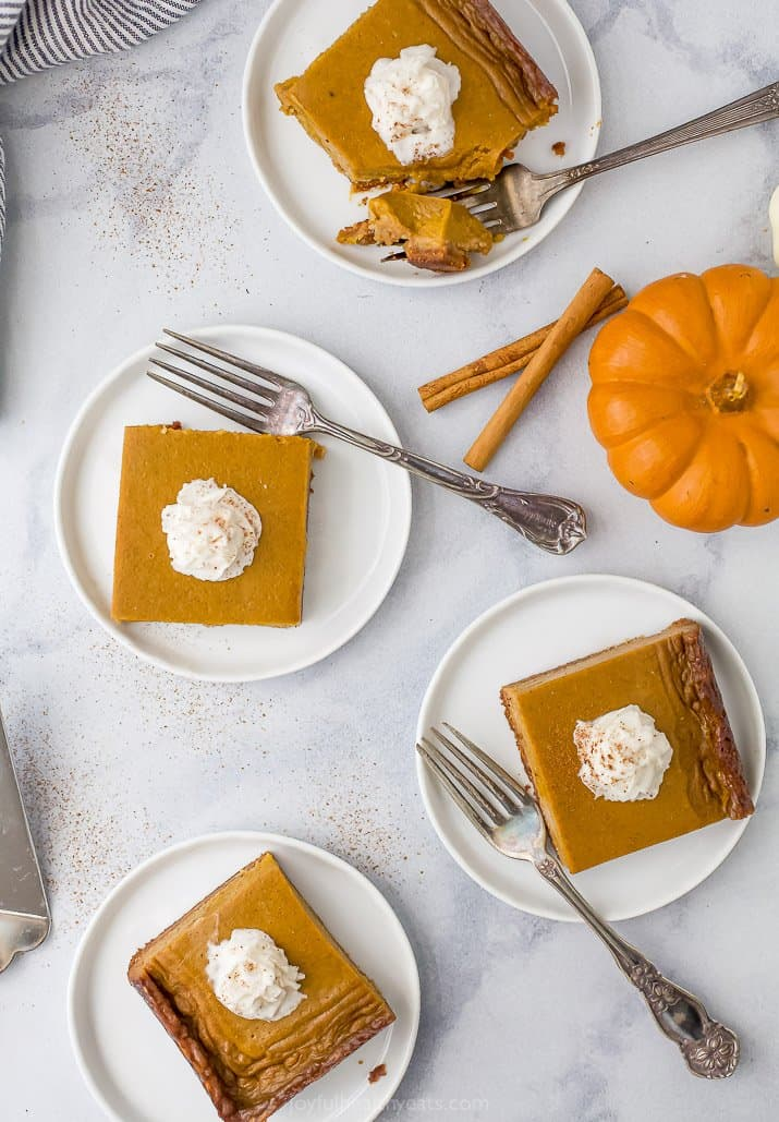 four plates with pumpkin pie bars on it