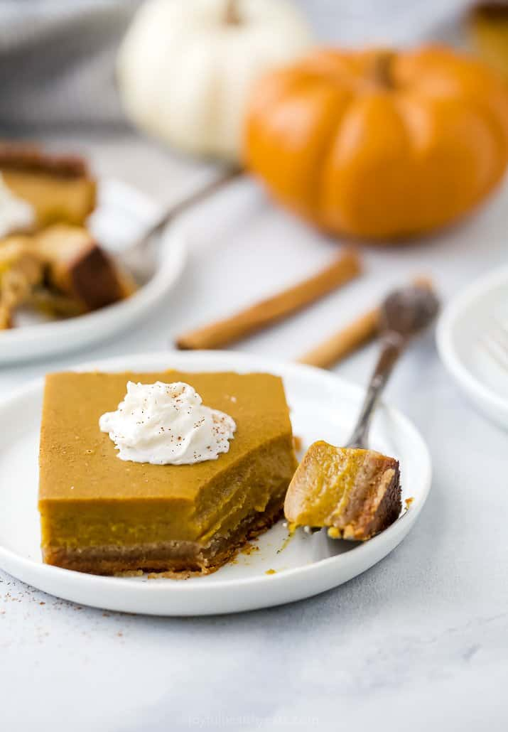 a plate with pumpkin pie bars with a fork on it