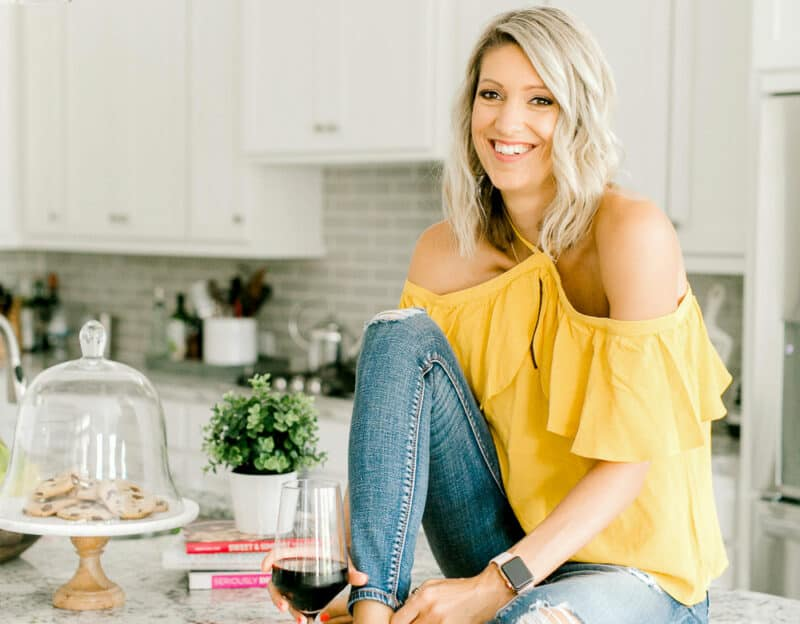 Krista sitting on a counter with a glass of wine