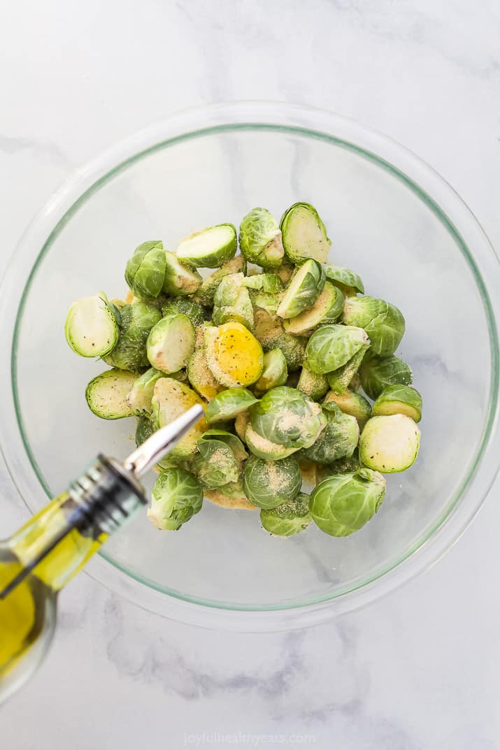 a bowl of brussel sprouts being seasoned