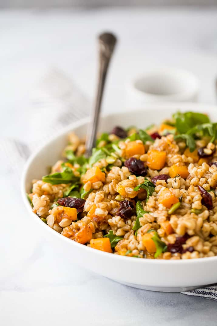 side photo of a bowl filled with fall farro salad and a spoon